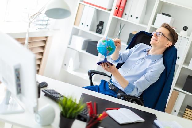 Un giovane si siede in ufficio alla scrivania del computer, chiude gli occhi e punta un dito verso il globo.