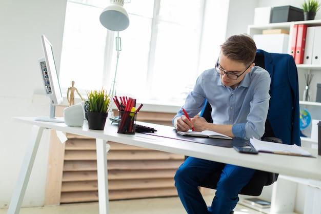 Un giovane si siede in ufficio alla scrivania di un computer e scrive su un quaderno.