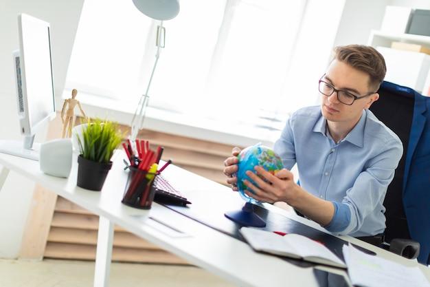 Un giovane si siede in ufficio alla scrivania di un computer e tiene in mano un globo.