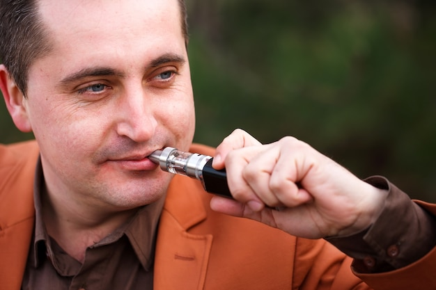 Un giovane si siede su una panchina e fuma una sigaretta elettronica.
