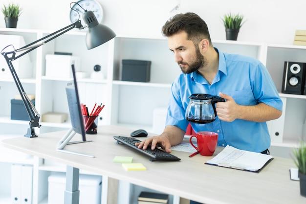 Un giovane si trova in ufficio al tavolo del computer e prepara il suo caffè.