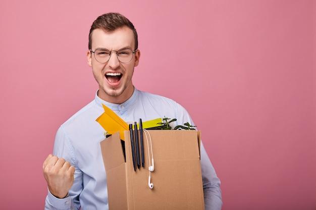 Un giovane simpatico ragazzo con una scatola di cartone con penne, pianta e aeroplanino di carta in mano come licenziato