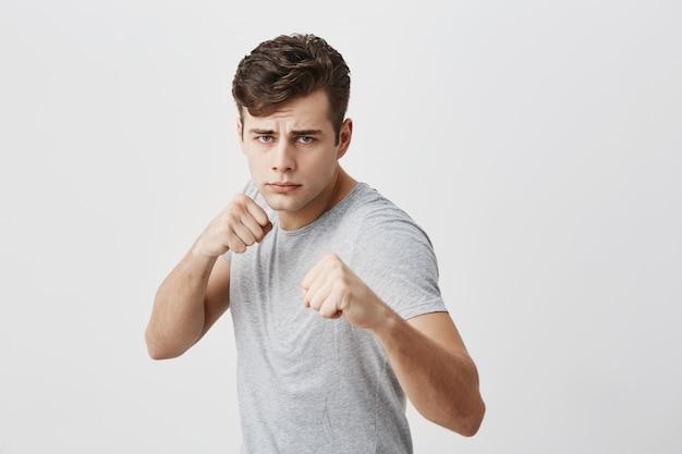 Un giovane sportivo muscoloso, serio e fiducioso, aggrotta la fronte per il dispiacere, mostra i pugni chiusi, dimostra forza e irritazione, pronto a difendersi. concetto di potenza e forza.