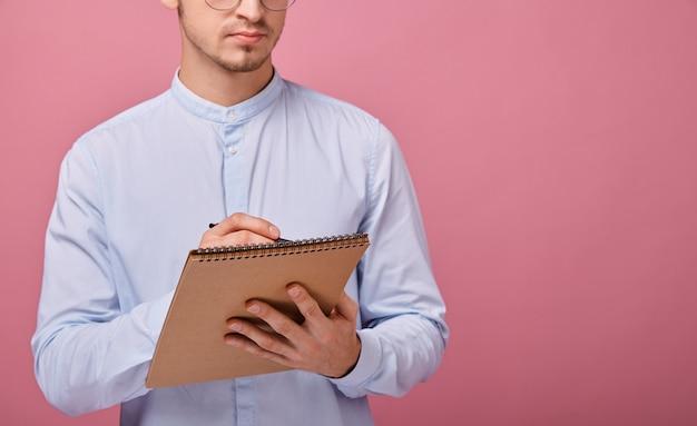 Un giovane studente in camicia azzurra con lavagna a fogli mobili marrone in una mano e una penna a sfera nera nell'altra