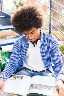 Un giovane studente maschio afro leggendo il libro all'aperto