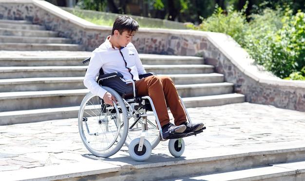 Un giovane su una sedia a rotelle che non riesce a scendere le scale.