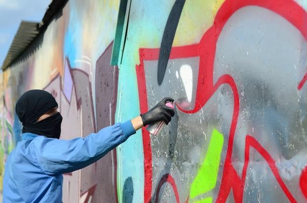 Un giovane teppista con una faccia nascosta dipinge graffiti su una parete di metallo. concetto di vandalismo illegale