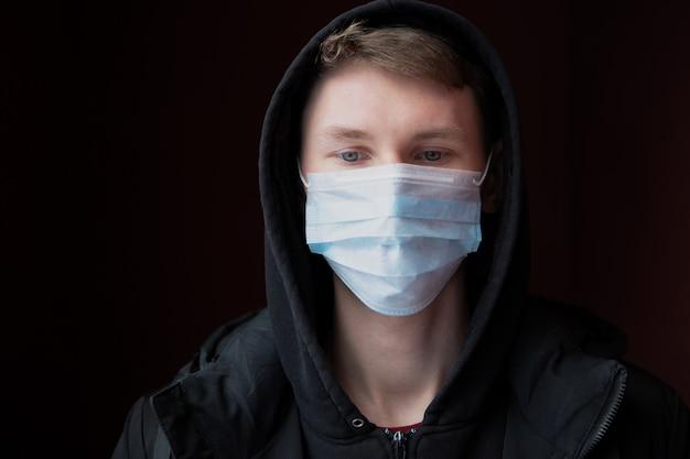 Un giovane triste protetto dal coronavirus da una mascherina medica abbassa tristemente lo sguardo.