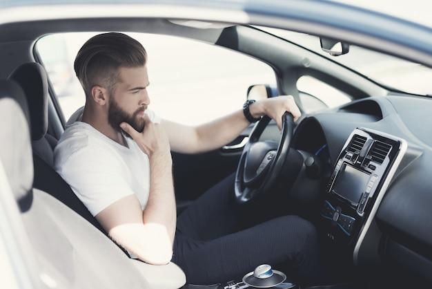Un giovane un po 'nervoso quando guida su strada.