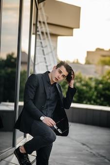 Un giovane uomo alla moda si trova vicino a un edificio a specchio durante il tramonto. moda