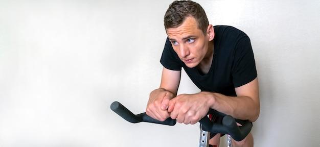 Un giovane uomo attraente impegnato su una bicicletta a casa su uno sfondo bianco, copia dello spazio