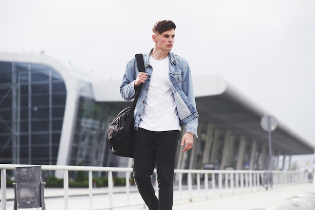 Un giovane uomo bello all'aeroporto sta aspettando il volo.