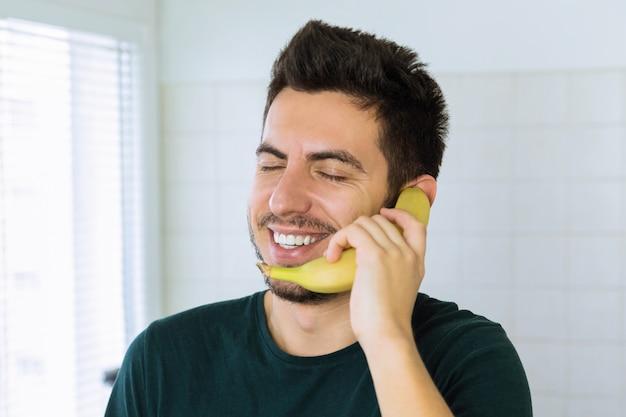 Un giovane uomo bello bruna sta parlando al telefono, invece di usare una banana. fotografia concettuale.