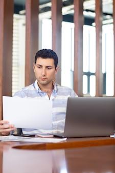 Un giovane uomo bello di vista frontale in camicia a strisce che lavora dentro la sala per conferenze usando il suo computer portatile d'argento che guarda attraverso i documenti durante la costruzione di attività di lavoro di giorno