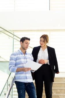 Un giovane uomo bello di vista frontale in camicia a strisce che parla e che discute i problemi del lavoro con la giovane donna di affari durante la costruzione di attività di lavoro di giorno