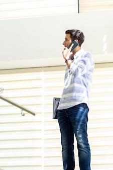 Un giovane uomo bello di vista frontale in camicia a strisce che parla e che discute le questioni di lavoro sul telefono durante la costruzione di attività di lavoro di giorno
