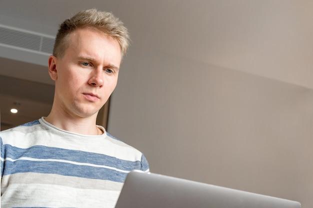 Un giovane uomo biondo sta lavorando a un laptop in camera con pareti bianche in hotel, viaggio d'affari