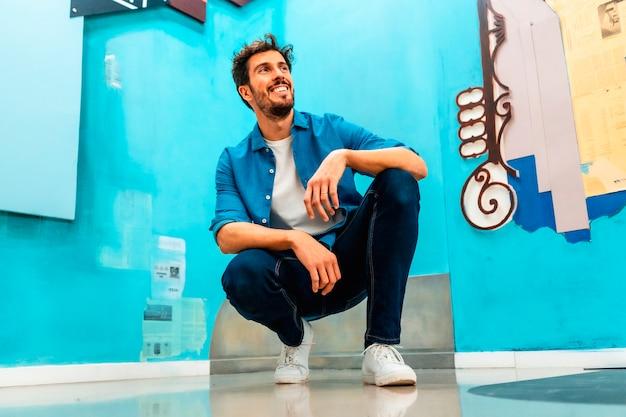 Un giovane uomo caucasico che sorride in una maglietta bianca e una giacca di jeans