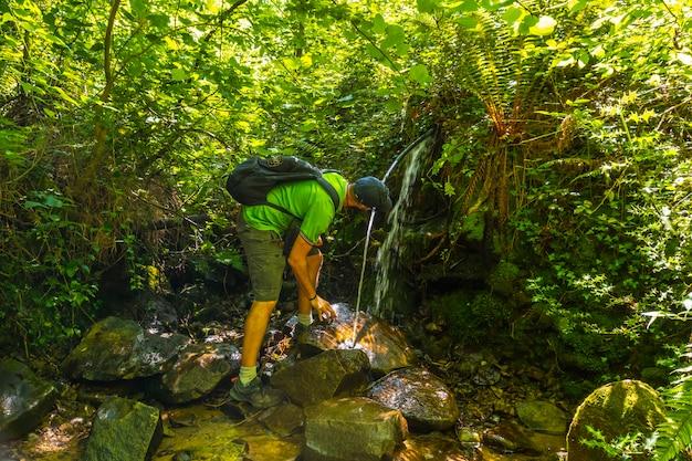 Un giovane uomo che beve acqua da una fonte naturale nel monte igueldo, guipuzcoa,