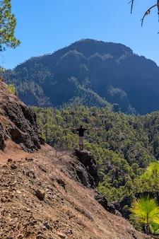 Un giovane uomo che guarda il paesaggio durante il trekking dalla cima di la cumbrecita accanto alle montagne della caldera de taburiente, l'isola di la palma, isole canarie, spagna
