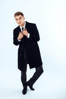 Un giovane uomo che indossa un cappotto. il concetto di moda.