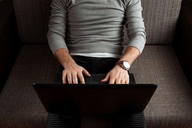 Un giovane uomo che lavora su un computer portatile rilassante su un comodo divano a casa in jeans.