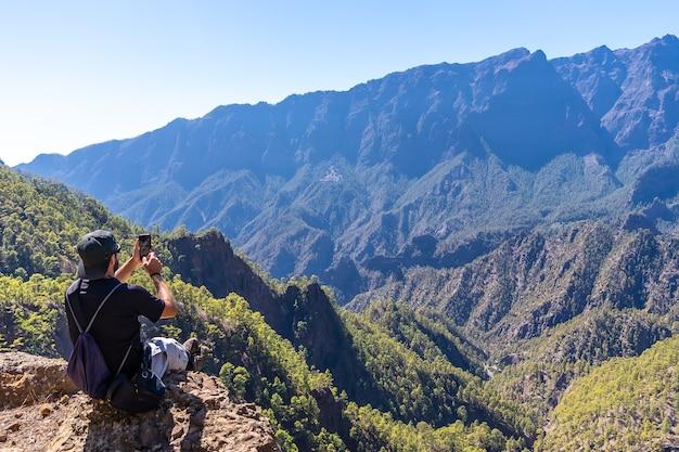 Un giovane uomo che riposa dopo il trekking in cima la cumbrecita seduto nel punto di vista naturale e scattare una foto con il cellulare, isola di la palma, isole canarie, spagna
