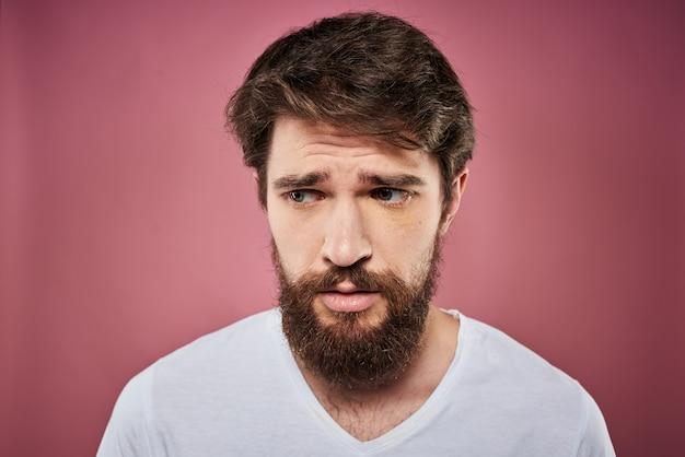 Un giovane uomo con la barba in una maglietta mostra diverse emozioni, divertimento, tristezza, rabbia in studio sullo sfondo