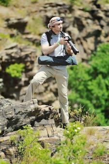 Un giovane uomo con una macchina fotografica spara la natura sullo sfondo di rocce e cielo