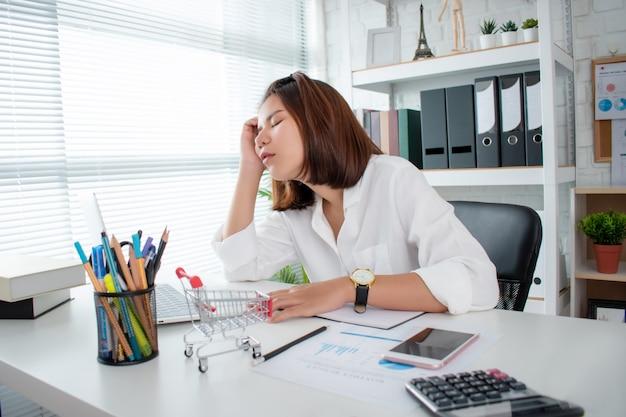 Un giovane uomo d'affari asiatico lavora duro ed esausto, dormendo segretamente con un computer portatile in una scrivania
