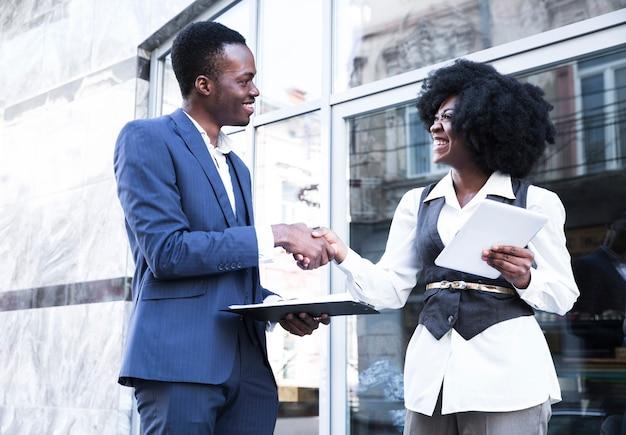 Un giovane uomo d'affari e una donna di affari africani che agitano le mani