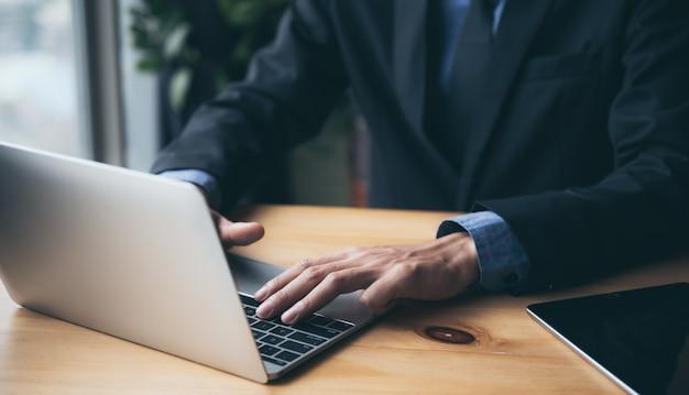 Un giovane uomo d'affari in abito nero sta lavorando su un laptop da una residenza privata, lavorando online per ridurre il rischio di infezione da virus.