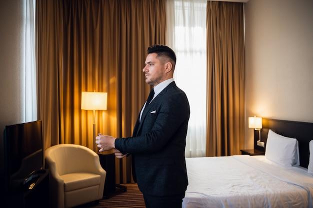 Un giovane uomo d'affari serio distoglie lo sguardo con fiducia, sistemandosi i polsini nella sua camera d'albergo, preparandosi ad uscire