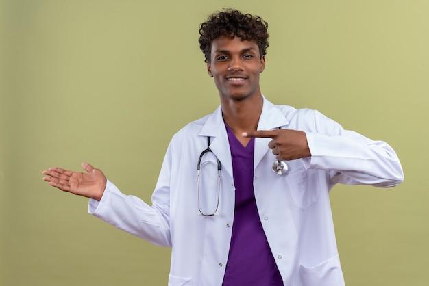 Un giovane uomo dalla carnagione scura bello con capelli ricci che indossa camice bianco con lo stetoscopio che punta con il dito indice su uno spazio verde