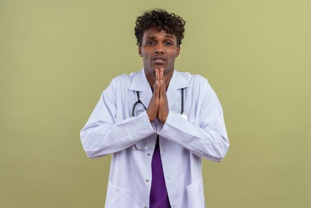 Un giovane uomo dalla carnagione scura bello con capelli ricci che porta camice bianco con lo stetoscopio che chiede scusa per qualcosa su uno spazio verde