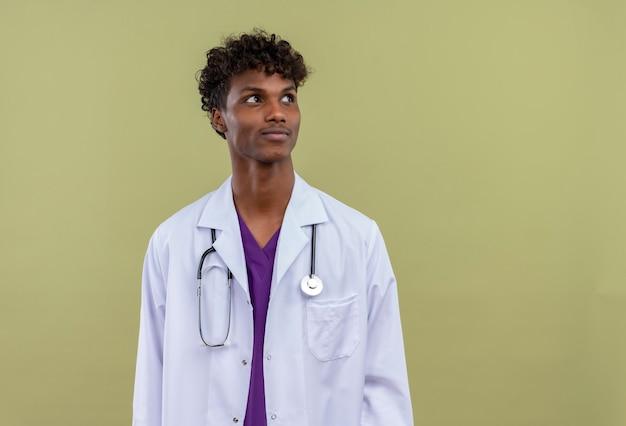 Un giovane uomo dalla carnagione scura bello con capelli ricci che porta camice bianco con lo stetoscopio che osserva in su sorprendentemente su uno spazio verde