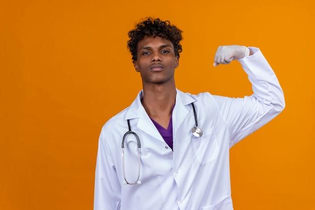 Un giovane uomo dalla carnagione scura bello con capelli ricci che porta il camice bianco con lo stetoscopio che solleva la mano con il pugno chiuso
