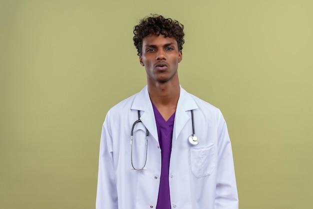 Un giovane uomo dalla carnagione scura bello con capelli ricci che porta il camice bianco con lo stetoscopio sorprendentemente su uno spazio verde