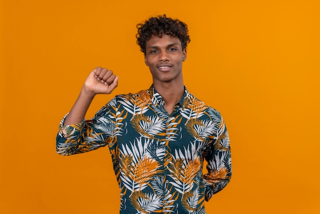 Un giovane uomo dalla carnagione scura bello con capelli ricci in camicia stampata foglie che sorride alzando la mano con il pugno chiuso