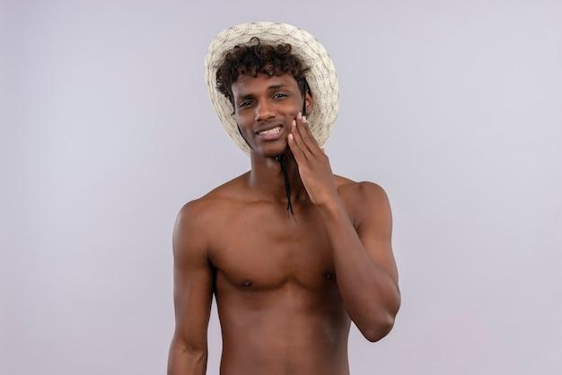 Un giovane uomo dalla carnagione scura bello dispiaciuto con capelli ricci che porta il cappello del sole che tocca la guancia con la mano mentre