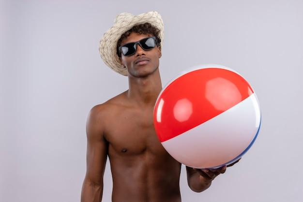 Un giovane uomo dalla carnagione scura bello fiducioso con capelli ricci che indossa cappello da sole e occhiali da sole mentre si tiene palla gonfiabile