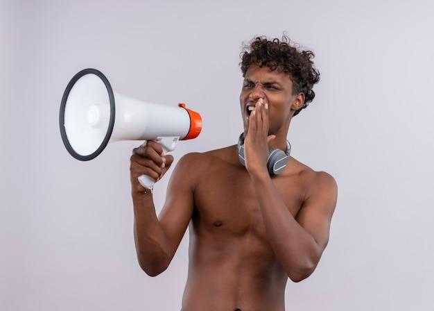 Un giovane uomo dalla carnagione scura bello serio con i capelli ricci che indossano le cuffie che parlano ad alta voce tramite il megafono