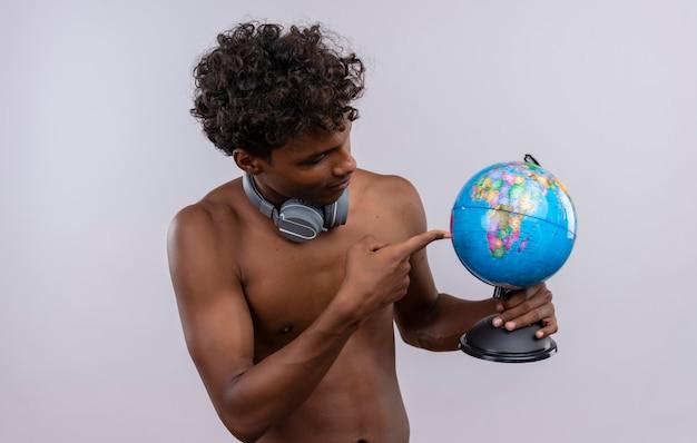 Un giovane uomo dalla carnagione scura bello serio con le cuffie da portare dei capelli ricci che indicano al globo con il dito indice