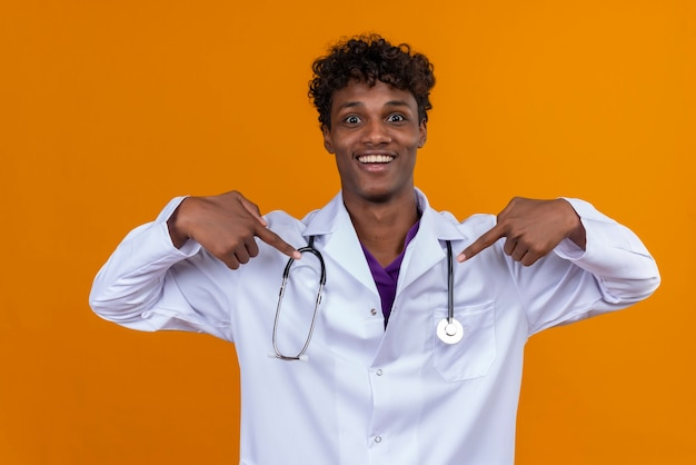Un giovane uomo dalla carnagione scura con capelli ricci che indossa camice bianco con lo stetoscopio che punta a se stesso con il dito indice