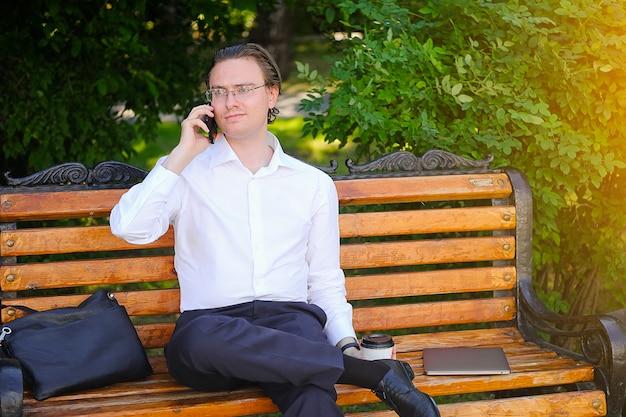 Un giovane uomo in camicia bianca e occhiali è al telefono nel parco.