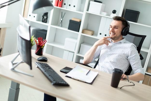 Un giovane uomo in cuffie si siede a una scrivania del computer