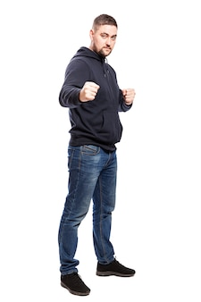 Un giovane uomo in jeans in una posizione di combattimento. a tutta altezza. isolato sul muro bianco. verticale.