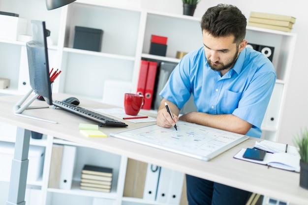 Un giovane uomo in piedi in ufficio alla scrivania di un computer e lavorando con una lavagna magnetica.