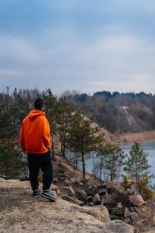 Un giovane uomo in piedi sul bordo di una scogliera