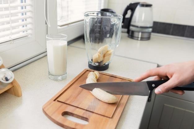 Un giovane uomo prepara un frullato di latte e frutta fresca per colazione. conduce uno stile di vita sano.